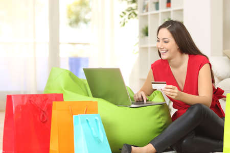 Woman buying online at home with a credit card and multiple shopping bags beside 스톡 콘텐츠