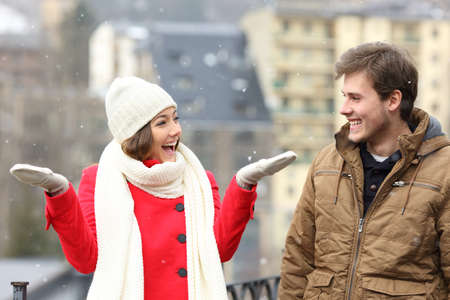 fashion boy: Happy couple enjoying snow in a snowy day in the street of a town Stock Photo