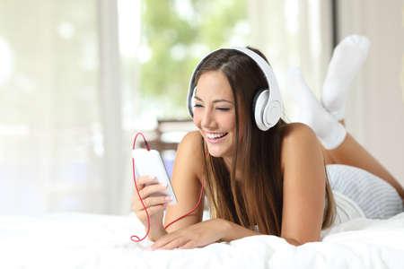 Gelukkig meisje luisteren naar de muziek van een smartphone op het bed thuis