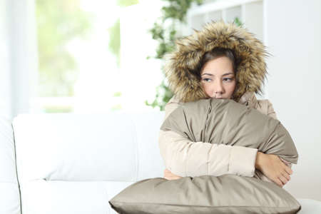 heat home: Angry woman warmly clothed in a cold home sitting on a couch
