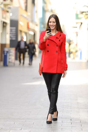 adult  body writing: Fashion woman wearing red jacket texting a smart phone in winter walking in the street