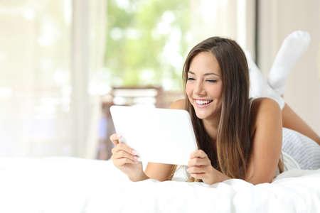 mujer viendo tv: niña feliz ver vídeos en una tableta tumbado en la cama en su casa