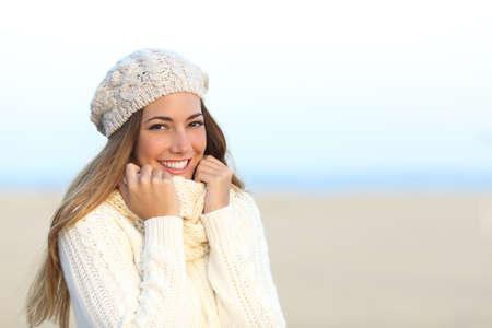 温かみのある笑顔の女性は、ビーチで寒い冬に服を着たまま