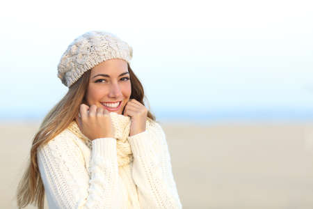 warmly: Woman smiling warmly clothed in a cold winter on the beach