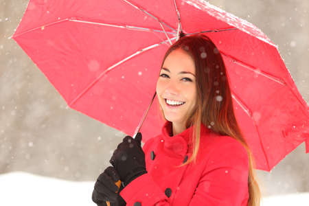 red gloves: Beauty woman in red with an umbrella in a snowy winter