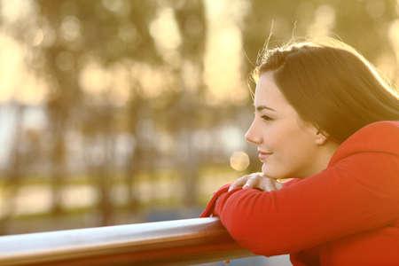 pensando: Menina relaxed pensativo que pensa no inverno olhando para a frente ao pôr do sol