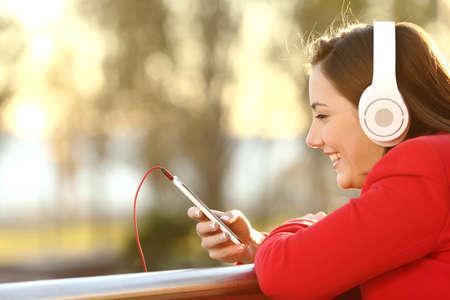 escuchar: Señora escuchar música desde el teléfono inteligente con auriculares al aire libre al atardecer en invierno