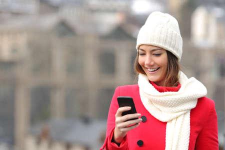 温かみのある通りに冬の服を着て携帯電話で女の子のテキスト メッセージ 写真素材