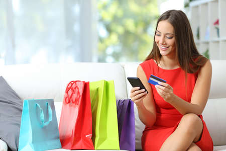 happy customer: Fashion girl buying online with smart phone and credit card with colorful shopping bags beside Stock Photo