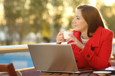 thinking woman: Entrepreneur with a laptop relaxing in a coffee shop and looking forward