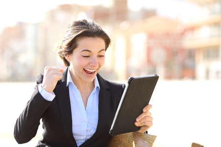 conclusion: Eufórico exitosa ejecutiva viendo una tableta que se sienta en un banco en un parque Foto de archivo