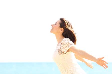 Gelukkige vrouw genieten van de wind en het inademen van frisse lucht op het strand op een zonnige en winderige dag