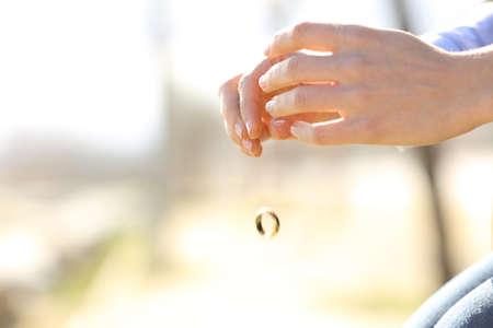 anillos de matrimonio: Sad mujer manos cayendo su anillo de bodas problemas en el matrimonio concepto