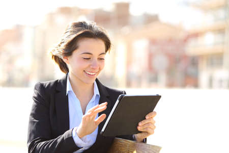 Executive working browsing a tablet in a park sitting in a bench