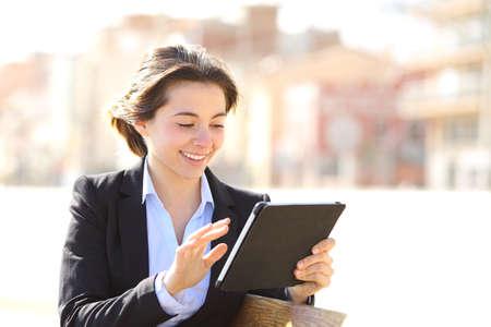 aprendizaje: Trabajo Ejecutivo consulta una tableta en un parque sentado en un banco Foto de archivo