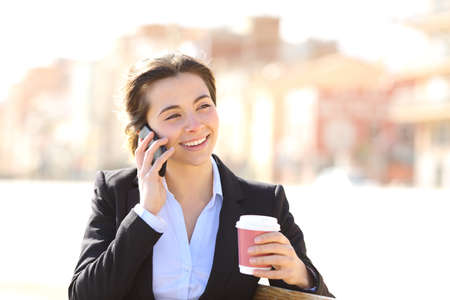 telephone saleswoman: Business woman on the phone sitting in a bench in a park with a coffee cup