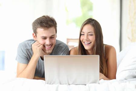 Vista frontal de una pareja de risa mientras ve los medios de comunicación en un ordenador portátil en casa
