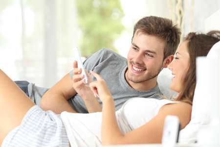 girl bed: Happy marriage sharing a smart phone on the bed at home