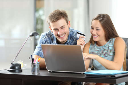 bank interior: Couple buying online together with a laptop on a desktop at home Stock Photo