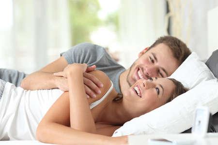 riendo: Feliz pareja coqueteando en la ma�ana en la cama en su casa
