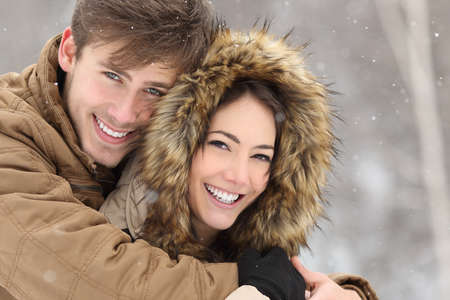 woman looking: Couple smiling with perfect teeth hugging and looking at camera in winter in a forest Stock Photo