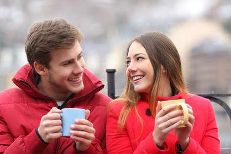 amantes: Pareja hablando relajado sentado en un banco con tazas de caf� en invierno