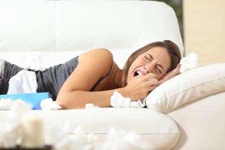 mujer llorando: Ni�a llorando desesperadamente acostado en un sof� en casa con un mont�n de toallitas Foto de archivo