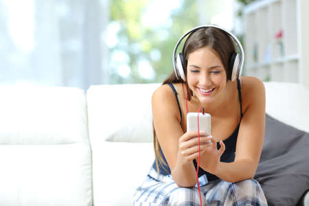 people listening: Happy girl listening music from smartphone with headphones in the living room at home