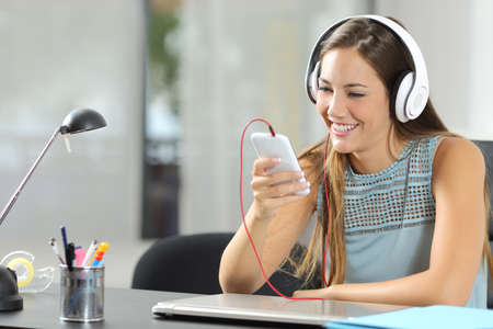 listening device: Girl listening to the music with a smartphone and headphones in her desktop at home