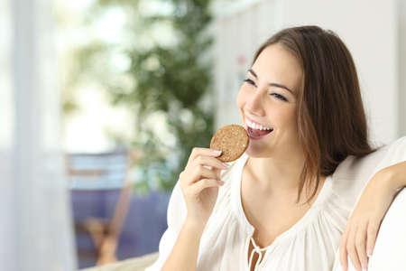 comiendo: Muchacha feliz que come una galleta dietética sentado en un sofá en casa