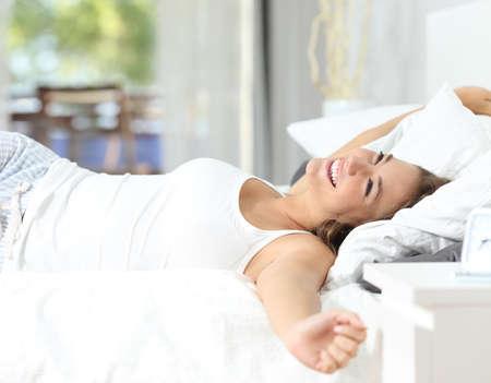 despertarse: Feliz niña despierta estirar los brazos en la cama en la mañana