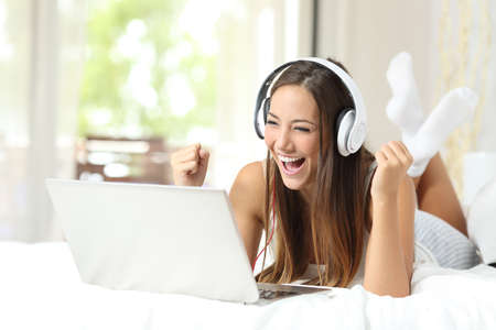 Euphoric winner girl watching media in a laptop on the bed at home Stock Photo