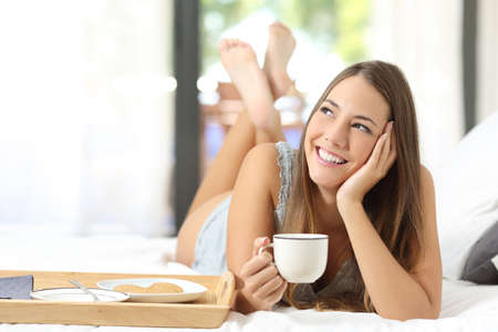women holding cup: Happy girl having breakfast holding a coffee cup lying on the bed and looking sideways