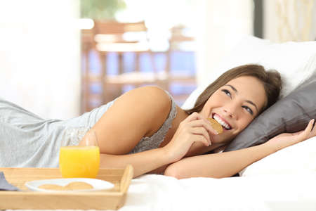 dietetic: Happy girl eating dietetic cookies at breakfast and thinking looking above lying on the bed at home