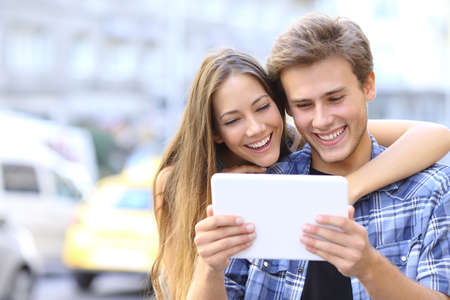 Happy couple or friends hugging and sharing a tablet in the street