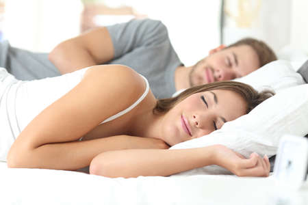 woman laying: Happy couple sleeping in a comfortable bed at home Stock Photo