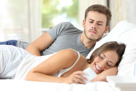 paying attention: Jealous gossip husband watching his wife mobile phone on the bed at home