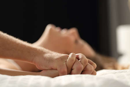 hot sex: Close up profile of a couple having sex on a bed at home in the night Stock Photo