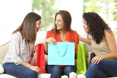 Compradores felices con bolsas de la compra hablando sentado en un sofá en casa