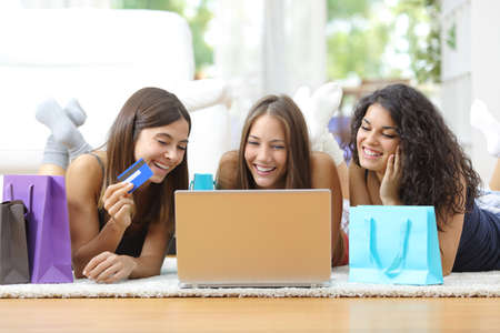 Drie vrienden die online winkelen met credit card en laptop liggend op de vloer thuis