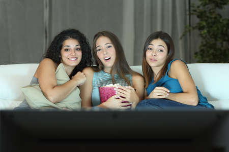 sofa television: Three friends watching romantic movie on tv sitting on a couch at home Stock Photo