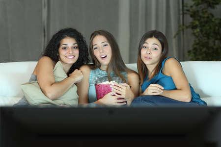 personas viendo television: Tres amigos que miran película romántica en la televisión sentado en un sofá en casa