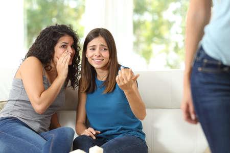 chismes: Dos amigos de chismes criticando a otra mujer en el hogar Foto de archivo