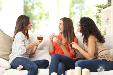 Three happy friends talking and drinking coffee and tea sitting on a couch at home