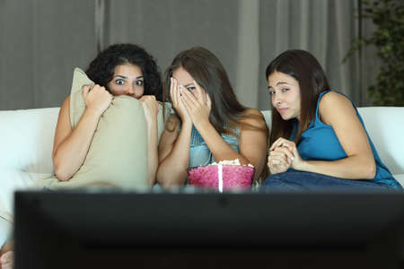 Girls watching a terror movie on tv sitting on a couch at home
