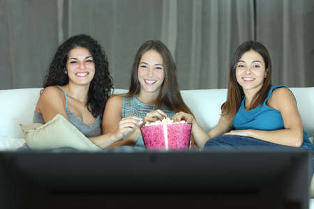 eating popcorn: Three happy friends watching tv sitting on a couch at home