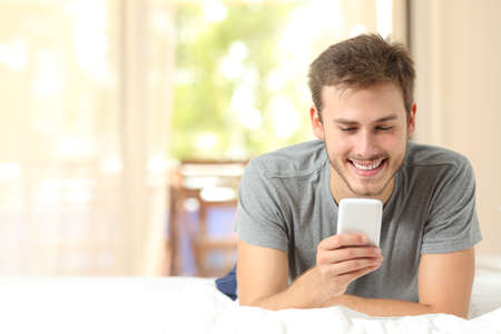 Front view of a guy using a mobile phone in the bedroom at home