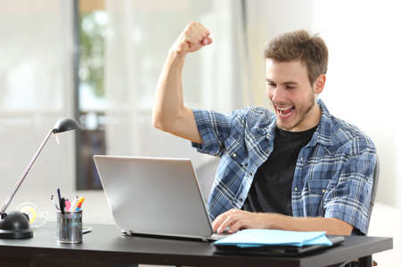Euforický vítěz šťastný muž pomocí přenosného počítače na stole doma