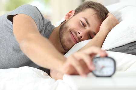 despertarse: Estela feliz plano de un hombre feliz acostado en la cama y detener el reloj de alarma Foto de archivo