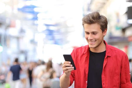 internet phone: Happy man in red texting on a mobile phone in the street